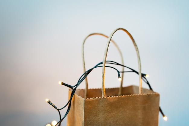 Подарочная упаковка поделки стоит на фоне рождественской гирлянды и боке