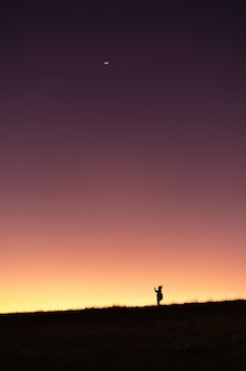 シルエット旅行夕焼け空グラデーションカラーの背景が付いている山の上に立っている人々。