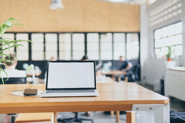 空白の画面の作業机の上のラップトップコンピューターがテンプレートをモックアップします。