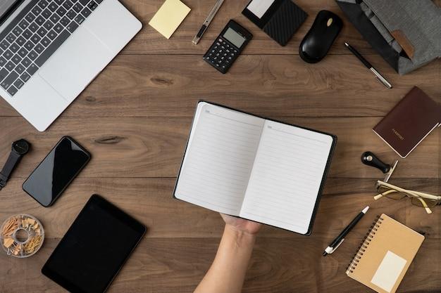 テーブルフラットのオフィスアクセサリーと空のノートブックリストに鉛筆を持っている手を置く