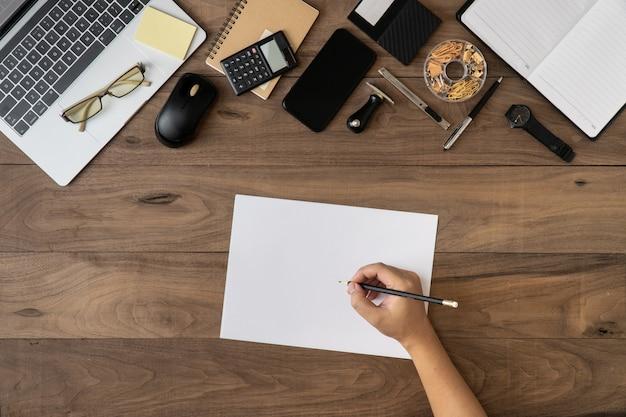 事務機器やビジネスアクセサリーの背景を持つ空の紙に鉛筆を持っている右手。