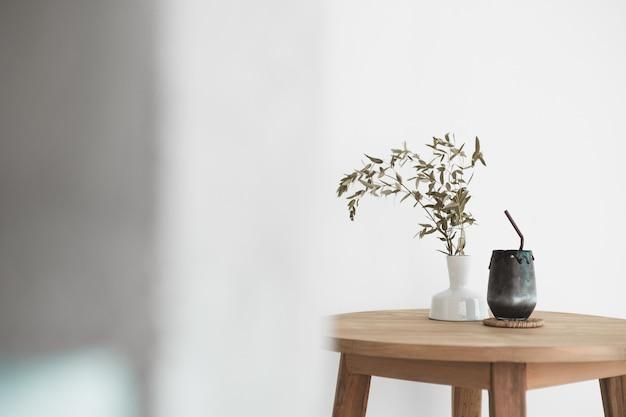 Черный напиток из древесного угля и молока на деревянный стол в винтажном стиле с сухим горшком для украшения листьев растений.