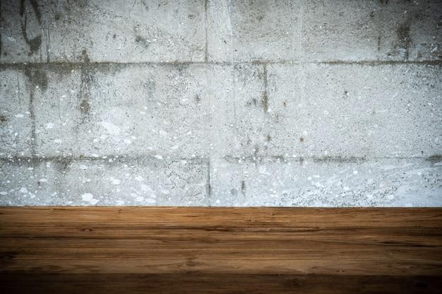 空の木のテーブルとグランジコンクリートスタイルの背景。挿入グラフィックとテキストオブジェクトのコピースペース。