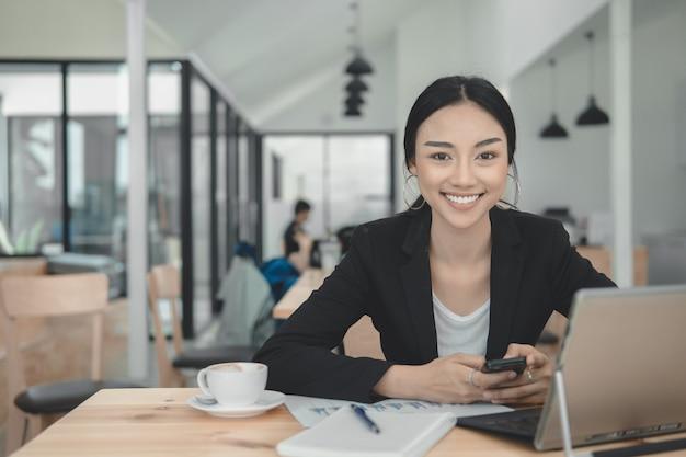 成功したビジネスウーマンのラップトップコンピューターに取り組んでいます。作業机の上のノートパソコンのキーボードを入力します。ビジネスプロフェッショナルな外観は、作業コンセプトをお楽しみください。