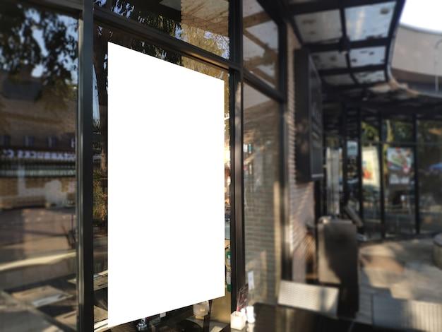 レストランのディスプレイでガラスに空白のポスターバナー。昇進の発表およびビジネス広告情報のための白い看板はモックアップします。