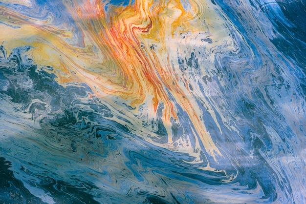 多色の油とガソリンの抽象的なイメージは、水に染みます。サイケデリックな背景