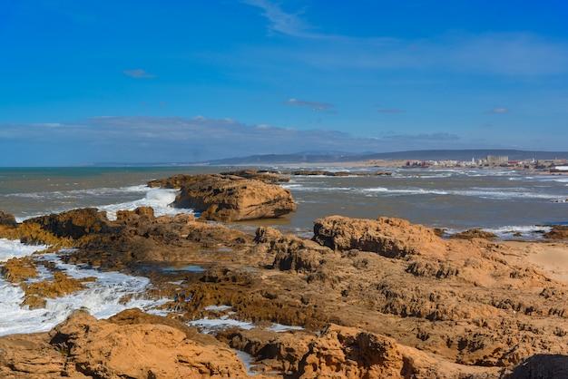 泡立つ波の岩のビーチ