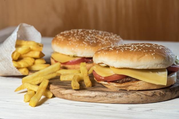 Два чизбургера с сочными говяжьими котлетами и салатом подаются с картофелем фри на пару