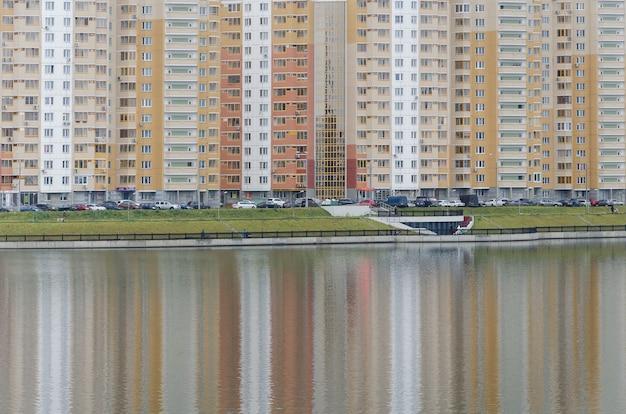 Ритмичное отражение разноцветных домов нового района москвы в пруду. цветовой баланс