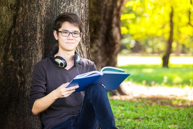 スマートな学生が教科書を読んで、リラックスして音楽を聞く