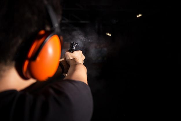 ピストル銃、射撃弾、射撃場でオレンジ色の耳掛けを着用している男