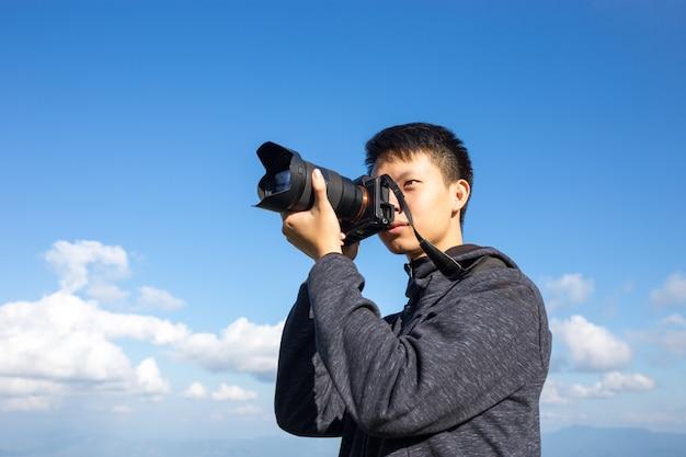 写真家は山の上に写真を撮っています