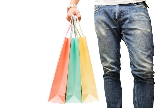 男はジーンズを着て、孤立した背景に手にカラフルなショッピングバッグを持っています