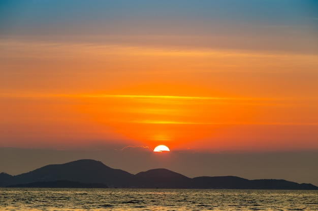 山と海の後ろに夕日と海の風景