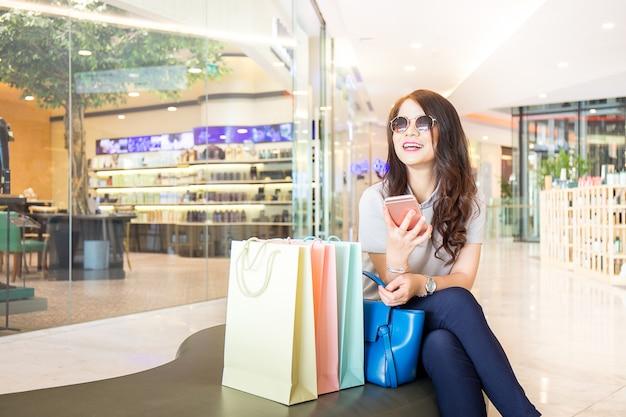 幸せな女は、ショッピングセンターで買い物袋を持つスマートフォンをプレイします。