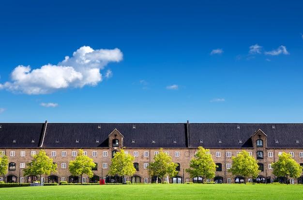 澄んだ青い空とコペンハーゲンデンマーク、ヨーロッパの芝生の芝生の古典的なアパート
