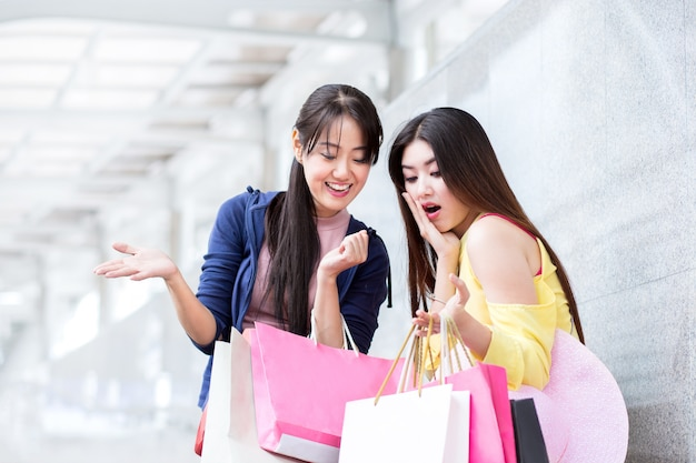 幸せなショッピング女性または友人、ダウンタウンの店の夏のセールで買い物袋を持つ女性