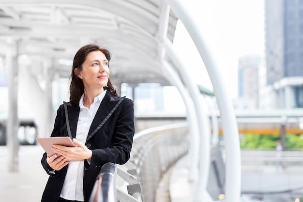 笑顔のビジネス女性は、ダウンタウンの歩道にタブレットを保持