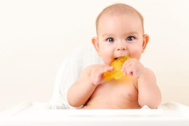 かわいい赤ちゃんの幼児の子供は、座っているハイチェアをかむ