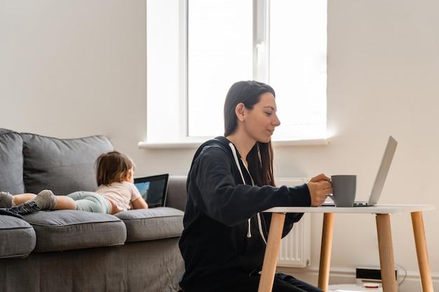 Молодая женщина, работа на дому. ребенок смотрит мультфильмы на планшете. работа на дому