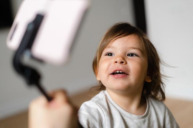 祖父母を呼び出すために自分撮り棒で電話を使用して幼児の女の子