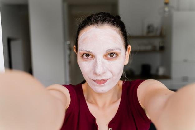 Кавказская женщина с лицевой маской в прямом эфире в качестве блогера красоты