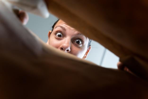 Кавказская женщина заглядывать в крафт-бумаги доставки пакета с удивлением эмоций.
