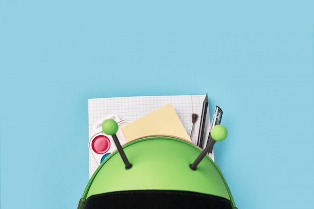 学校の文房具と緑のバックパックの平面図です。就学前の学校に戻る