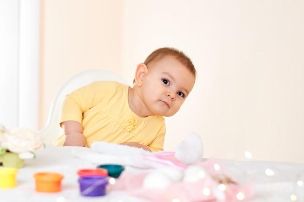 Девочка сидит за столом и рисует праздничные пасхальные яйца, улыбаясь счастливым детством