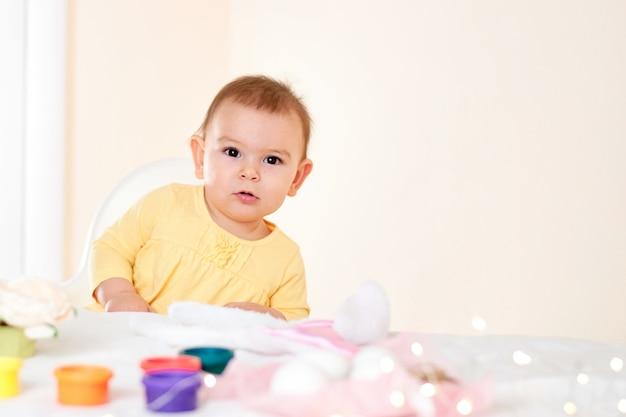 テーブルに座って、幸せな子供時代を笑顔の休日のイースターエッグを塗る女の赤ちゃん