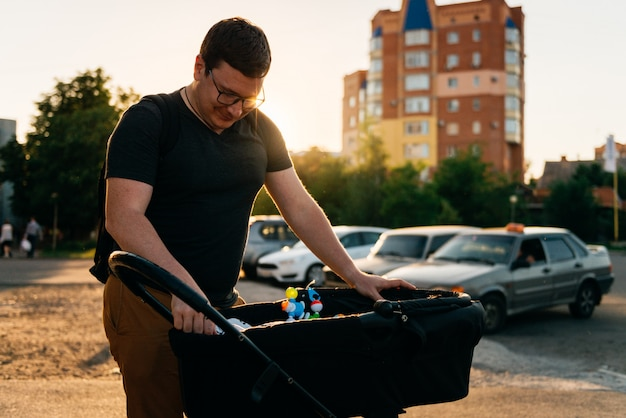 夏の夕暮れ時の外で生まれたばかりの乳母車ベビーカーと父親のお父さん