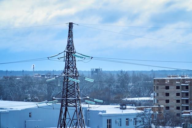 雪に覆われた高電圧がいしを有する送電線タワー。冬時間