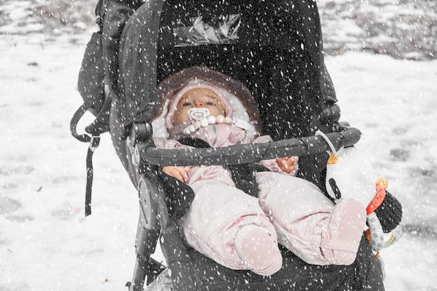 Малыш в детской коляске на свежем воздухе на снежной зиме