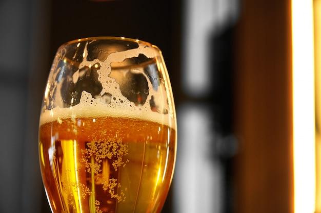 木製テーブルの上の影を落として、琥珀色の淡いエールビールのパイントグラスにクローズアップ