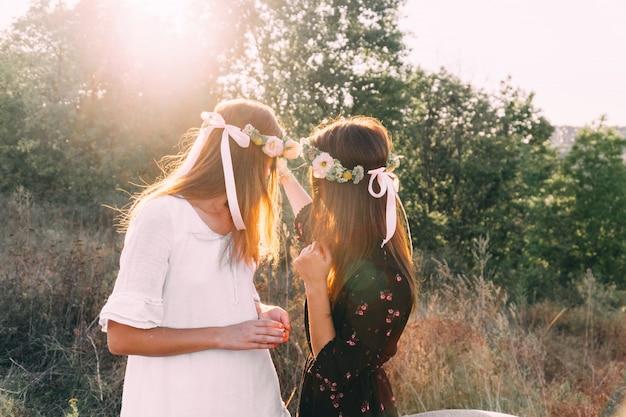 Две молодые девушки обнимаются во время заката в поле с бокалом дружбы