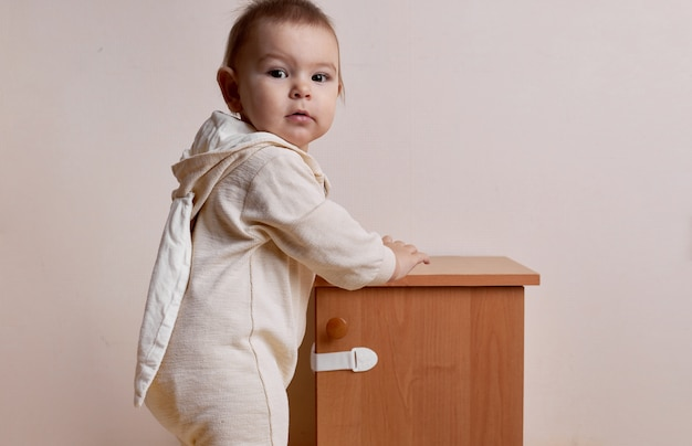 ベビープルーフロックでキャビネットを開こうとしている女の赤ちゃん