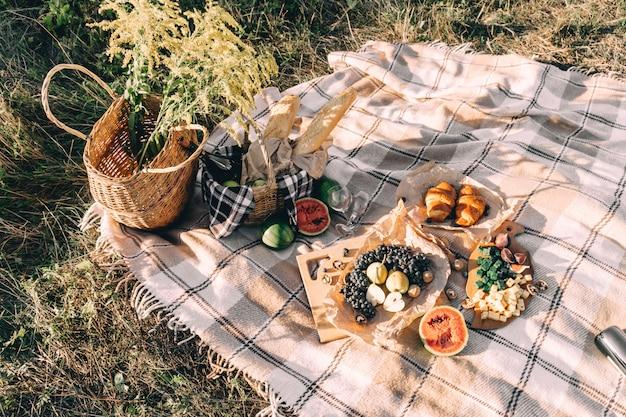 格子縞、食べ物や飲み物の概念のライフスタイルの晴天に日没時の夏のピクニック