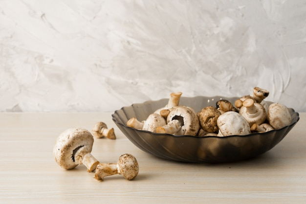 白の明るい木の皿にシャンピニオンキノコ