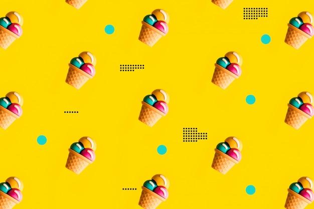 黄色の背景にカラフルなアイスクリームのパターン。