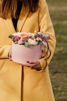 美しい女性の花とピンクのボックスを保持しています。女性の日への贈り物。