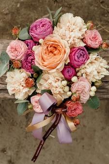 バレンタインデーの休日にピンクの弓と赤とオレンジ色のバラのトップビューの豪華な花束のトップビュー