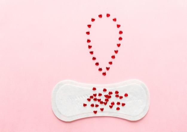 ピンク色の背景に女性用衛生パッド。月経時の婦人衛生の概念