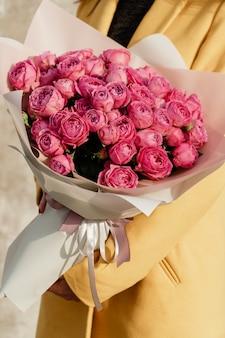黄色のコート、新鮮なピンクのバラの美しい開花の花の花束を保持している非常に素晴らしい若い女性の愛