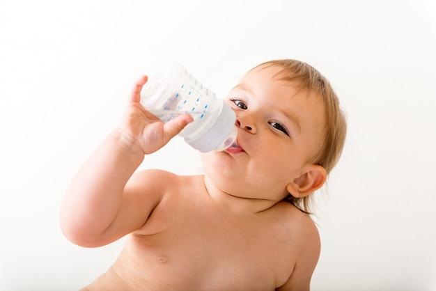 赤ちゃん幼児は白いベッドの上に座って、笑顔とペットボトルから水を飲む
