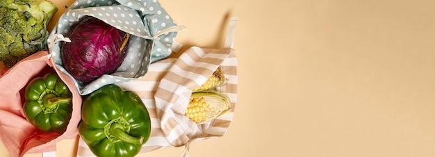 野菜が入った食料品用の布製コットンショッピングバッグ。ベージュ色の背景。プラスチックなし