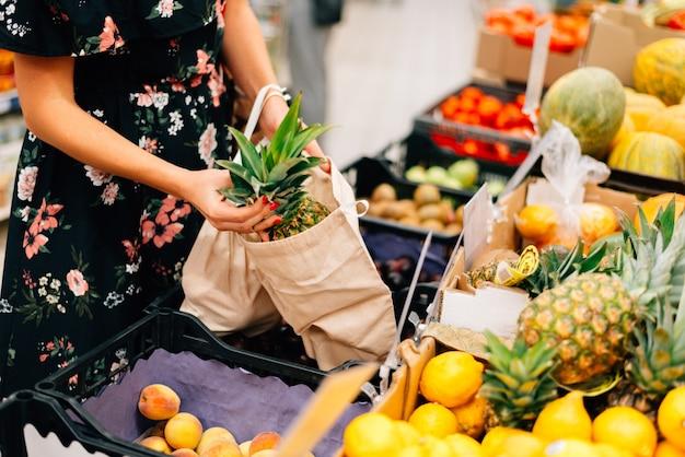 女性は果物と野菜の食料品市場を選ぶ
