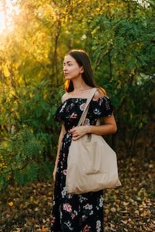 白人の女の子は日没の屋外でリネンの買物客を保持します