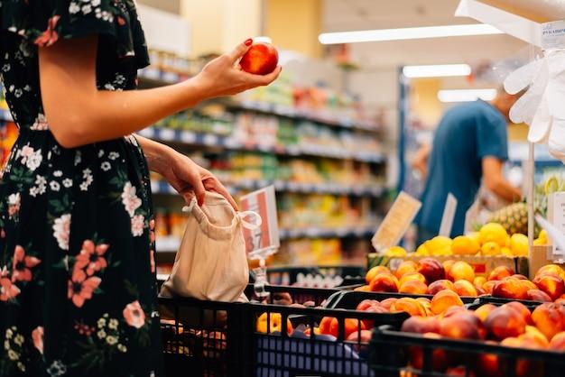 Женщина выбирает фрукты и овощи продовольственный рынок. многоразовая сумка для покупок. ноль отходов