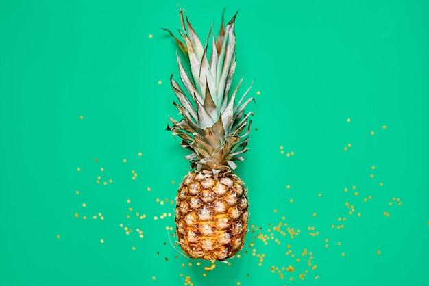 Сырой ананас с золотистым блеском. квартира лежала тропическая концепция