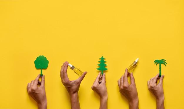 Руки держат эфирные масла и деревья. натуральная медицина плоская планировка. желтый